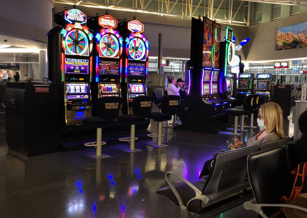 A passenger wearing a mask, right, sits about one of the near empty slot machine areas in Conco ...