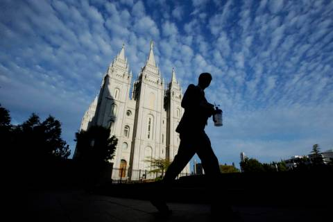 A man walks past the Salt Lake Temple, a temple of The Church of Jesus Christ of Latter-day Sai ...