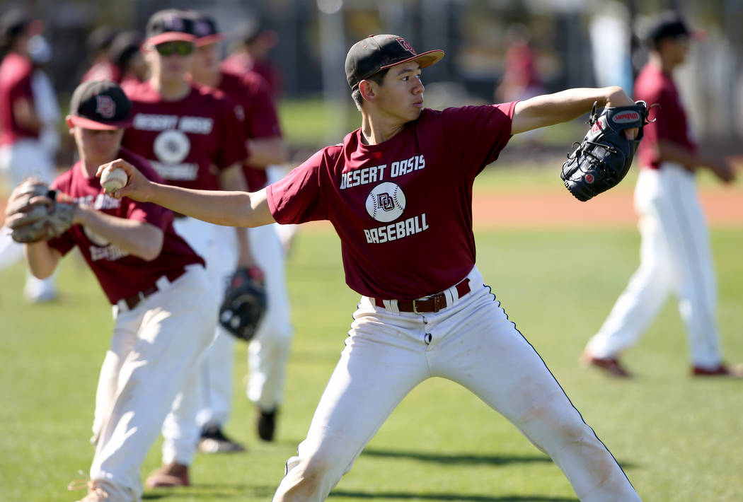 Desert Oasis baseball players, including pitcher Tyler Kennedy, warm up during a light practice ...