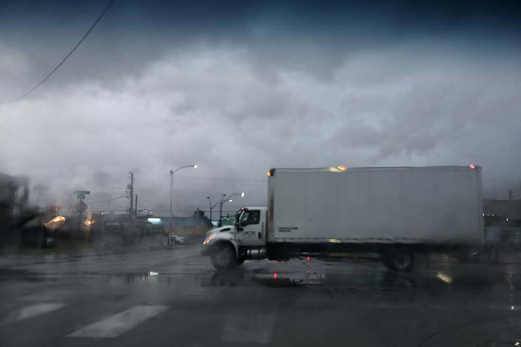 A truck drives through an intersection after heavy overnight rain in Las Vegas on Friday, March ...