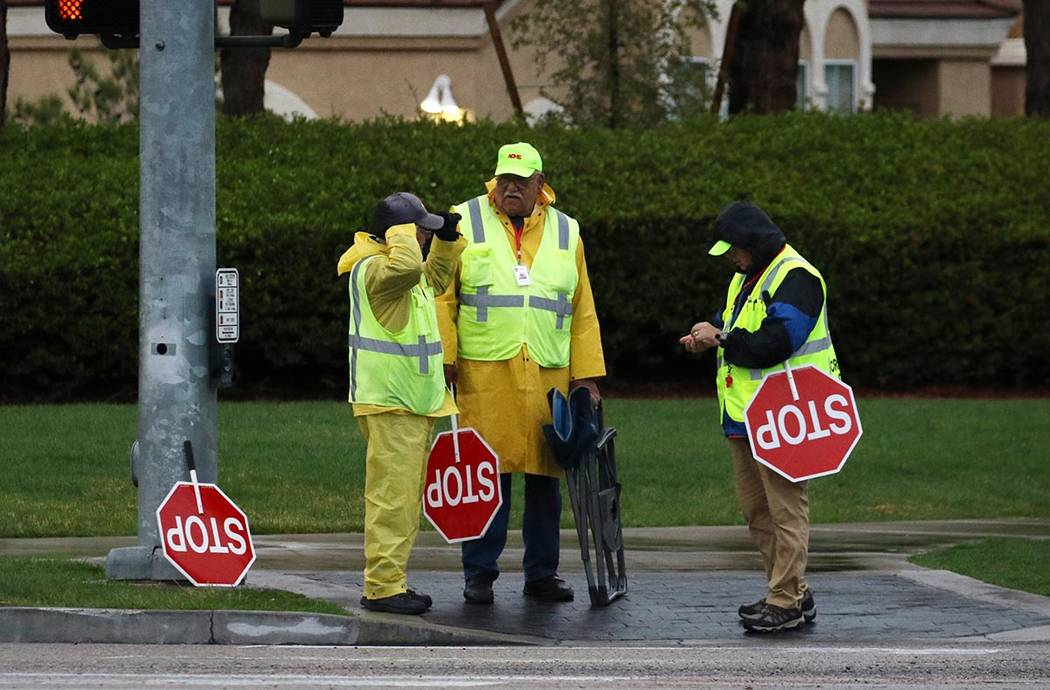 Crossing guards, wearing rain jackets, chat as they wait for students from Elise Wolff Elementa ...