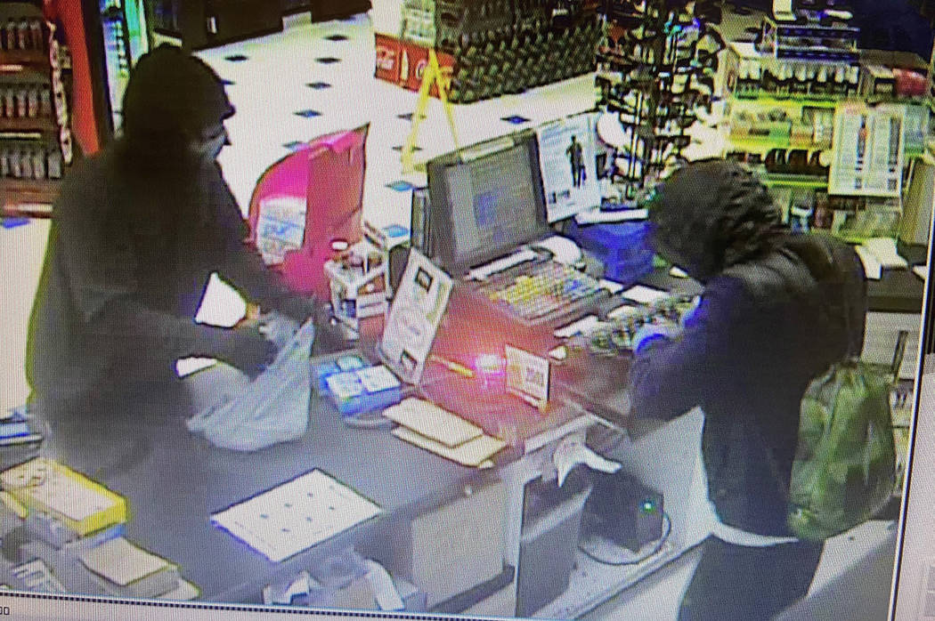 A still from video surveillance shows two men armed with AK47-like assault rifles stealing cash ...
