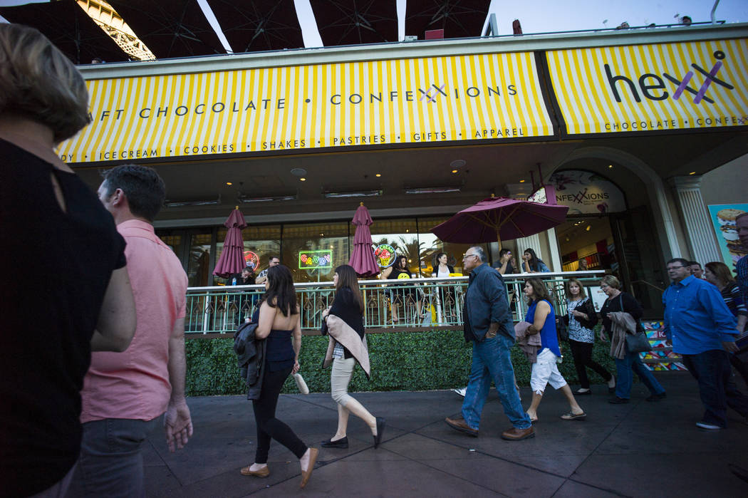 People pass Hexx restaurant outside of the Paris hotel-casino in Las Vegas on Friday, Nov. 4, 2 ...
