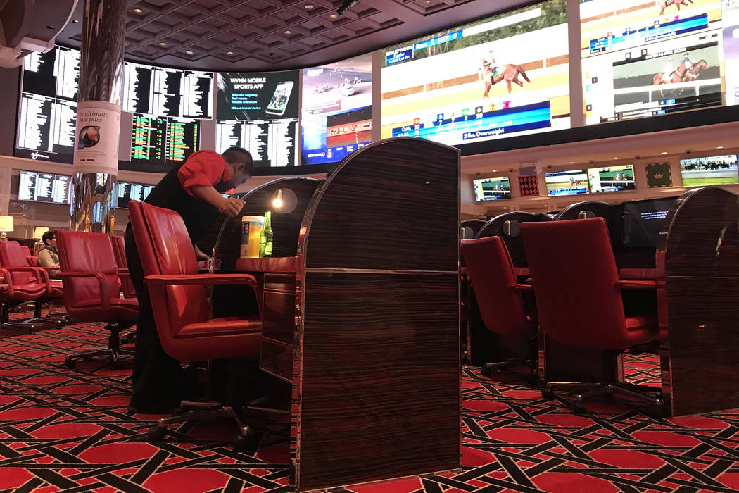 An employee wipes down chairs with Clorox wipes at Wynn Race & Sports Book on Friday, March ...