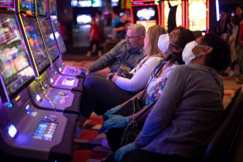 Gamblers wear masks and gloves in the midst of the coronavirus pandemic at Planet Hollywood on ...