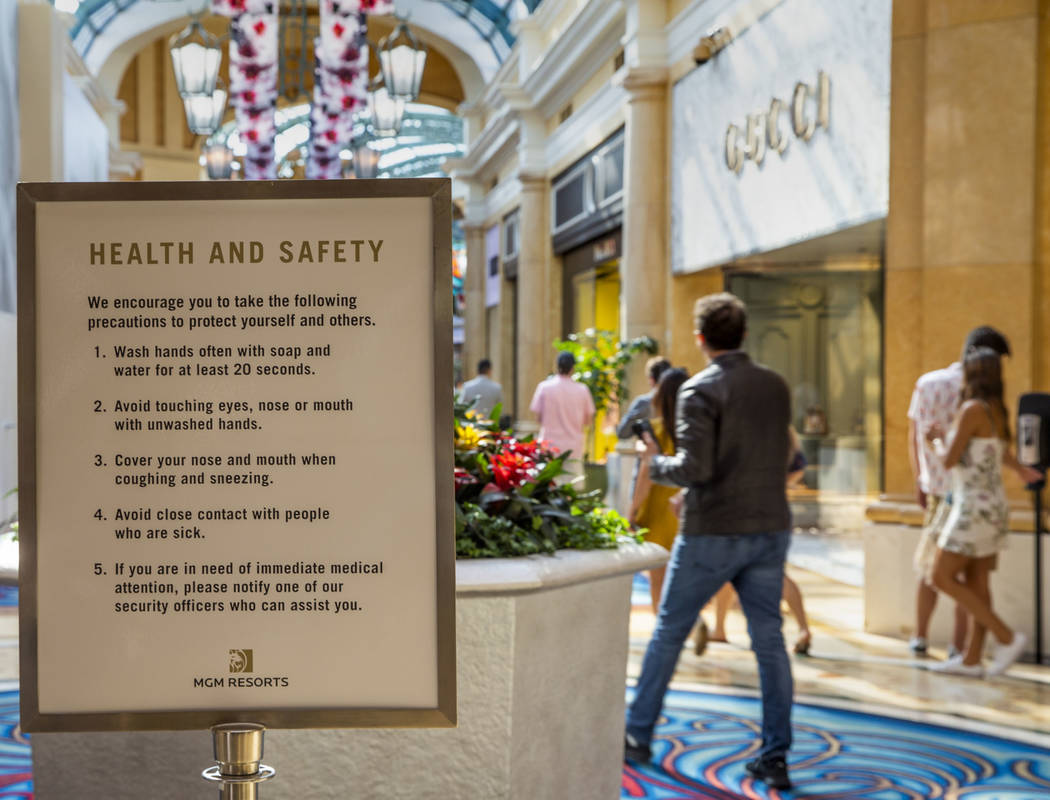 Health and safety guidelines greet visitors entering the shops at the Bellagio along the Strip ...