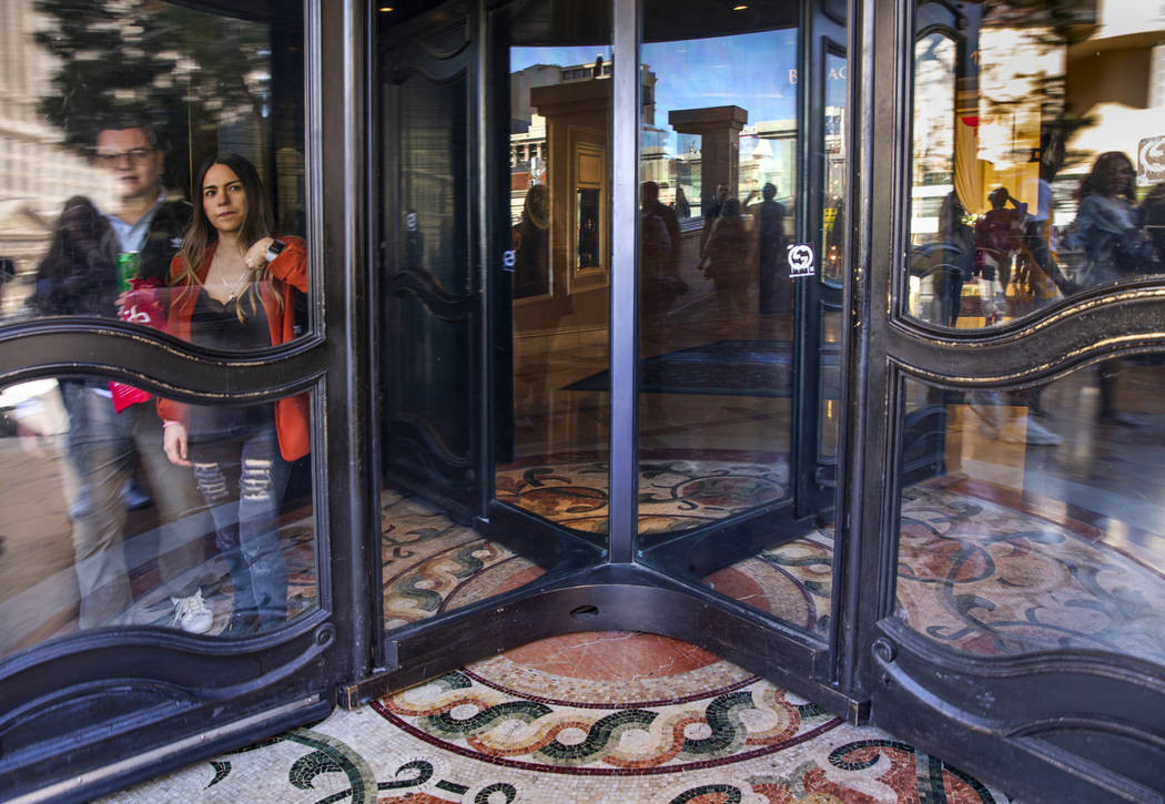 A visitor uses her elbow to push through a revolving door to avoid touching it while leaving th ...