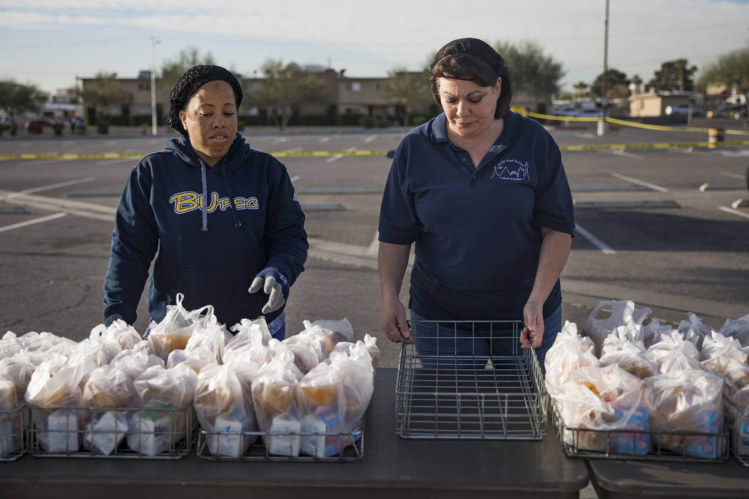 Clark County School District employees wait for families to pick up food at Clark High School i ...