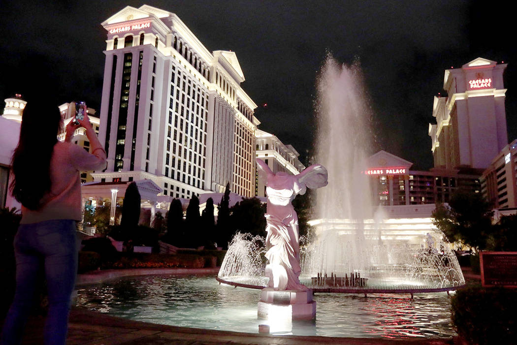 A woman takes a photo of Caesars Palace in Las Vegas, Saturday, March 14, 2020. ((Ellen Schmidt ...