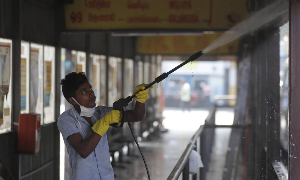 A Sri Lankan worker sprays disinfectant solution inside a bus terminal in Colombo, Sri Lanka, M ...