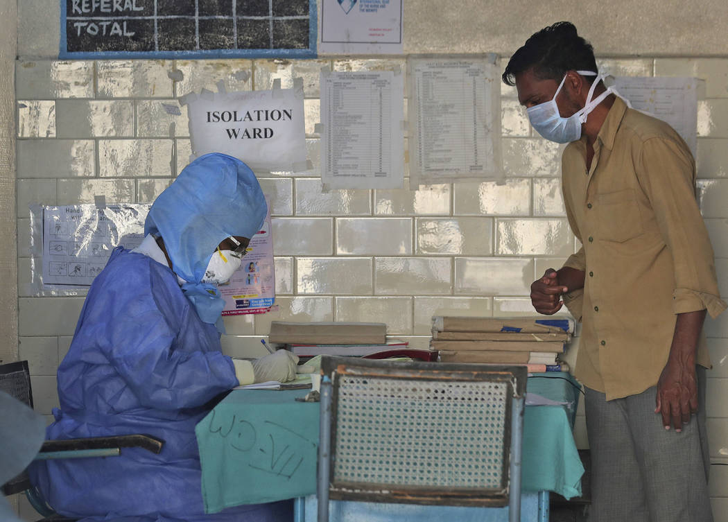 In this Sunday, March 15, 2020, photo, an Indian doctor in a protective suit sits outside an is ...
