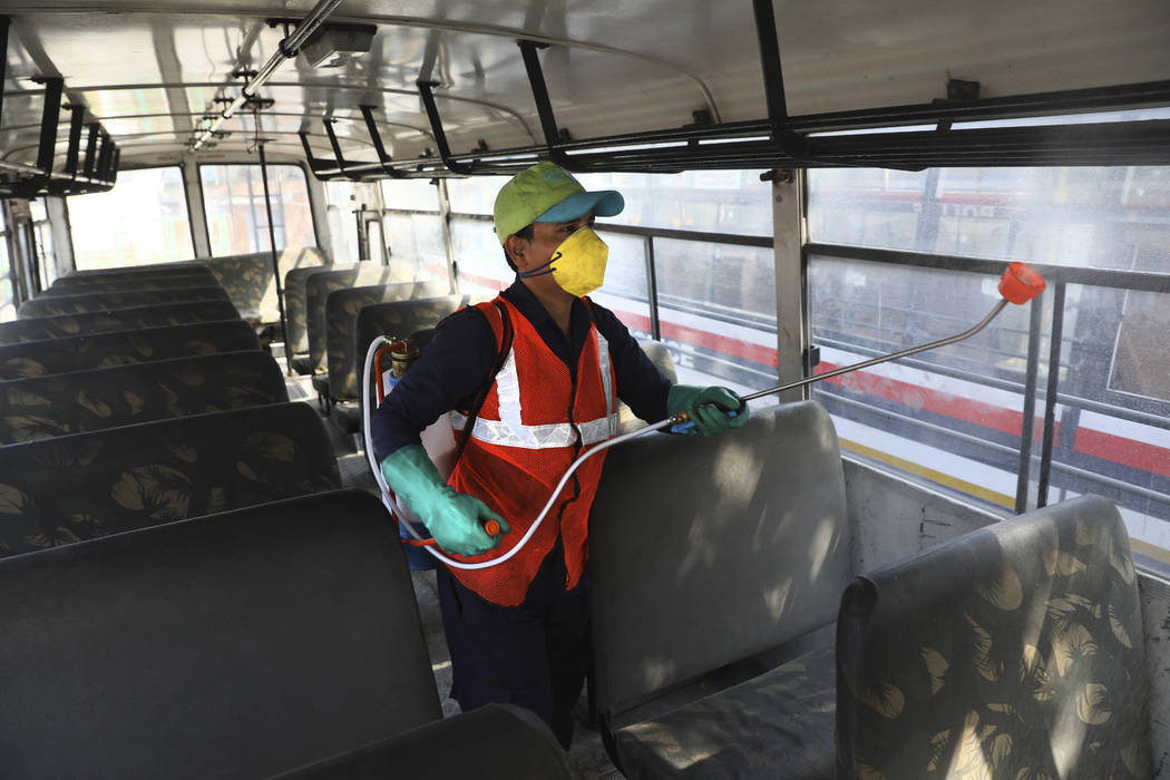 A worker disinfects a police bus as a precaution against COVID-19 in New Delhi, India, Monday, ...