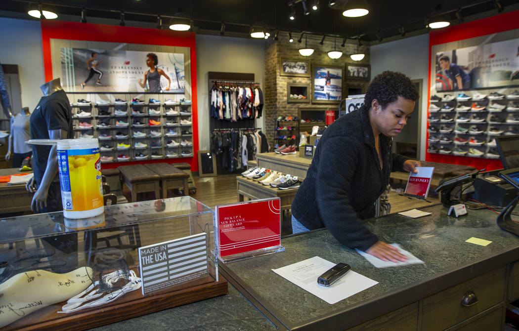 New Balance salesperson Heaven Fennell wipes down her counters and common areas at their Downto ...