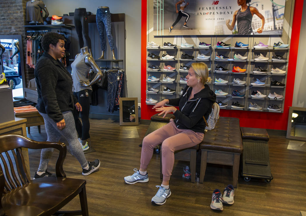 New Balance salesperson Heaven Fennell, left, works with customer Sandra Rivers at their Downto ...
