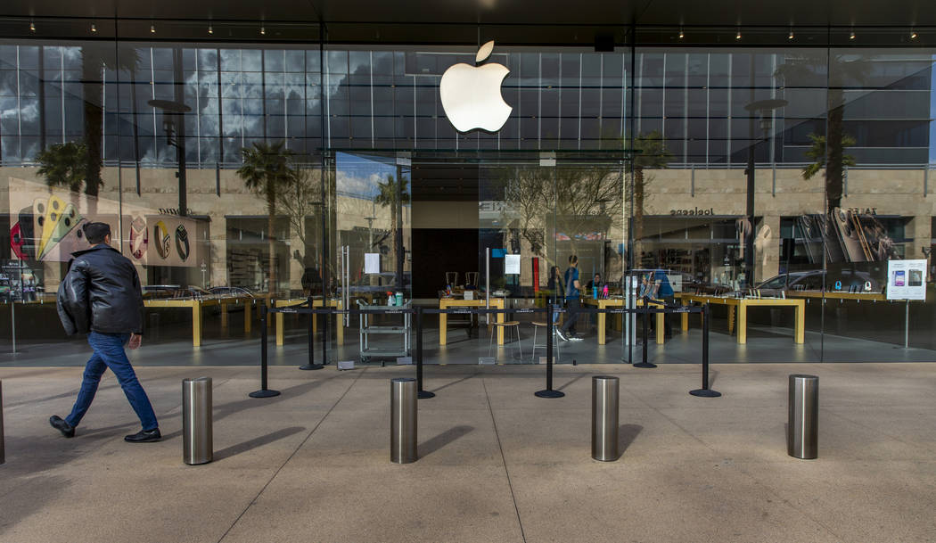 A passerby looks to the Apple Store now closed until March 27th at Downtown Summerlin which has ...