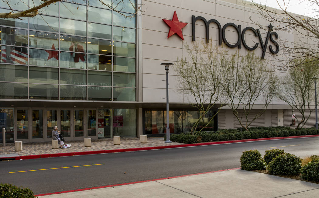 An elderly shopper sits outside of the Macy's store in Downtown Summerlin which has modified ho ...