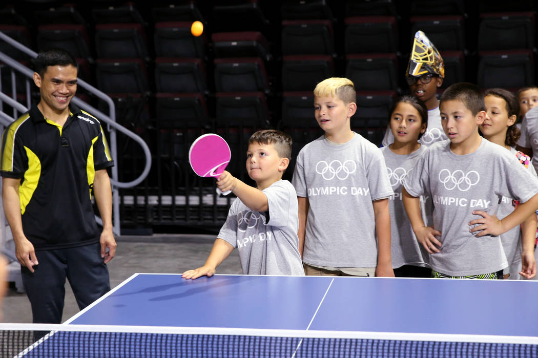 Luciano Sparacio, 8, plays table tennis as coach Jozon Lavilla, left, looks on during Olympic D ...
