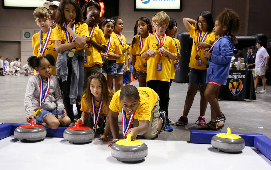 "Ishmael Edwards, 10, of John D. ""Jackie"" Gaughan Boys & Girls Club tries curling on Olympic Day ..."