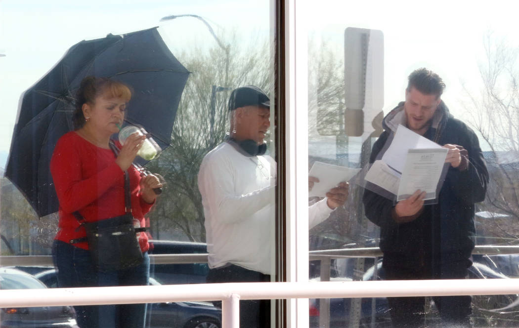 People are reflected on glass windows as they wait in line at One-Stop Career Center on Monday, ...