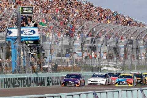 Denny Hamlin, left, leads the pack at the start of the NASCAR Cup Series championship auto race ...