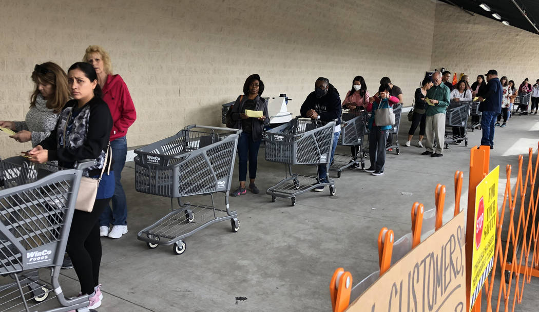 Customers wait in line at WinCo Foods on Monday, March 16, 2020, in Las Vegas. (Bizuayehu Tesfa ...