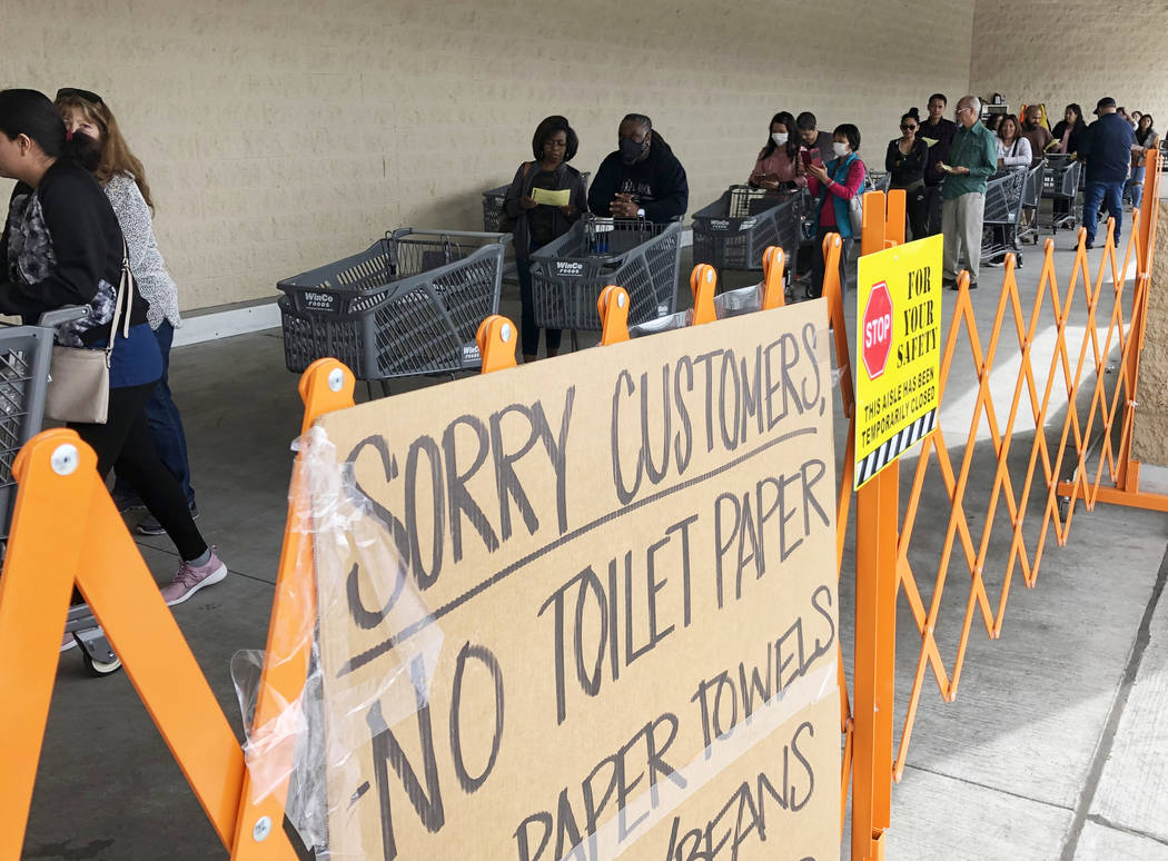 A list off sold out items are posted as customers wait in line at WinCo Foods on Monday, March ...