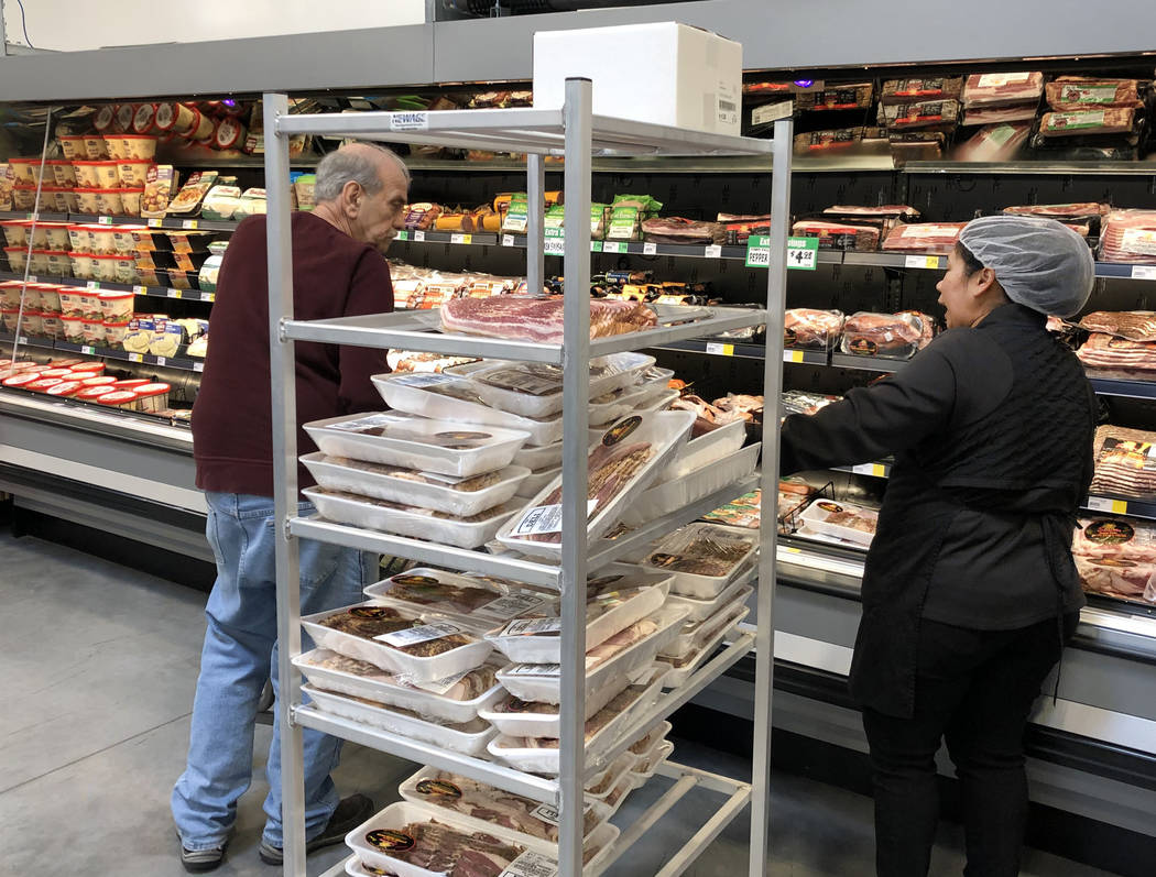 Nina Lopez, right, deli department manager, assists a customer as she stocks meat products at W ...