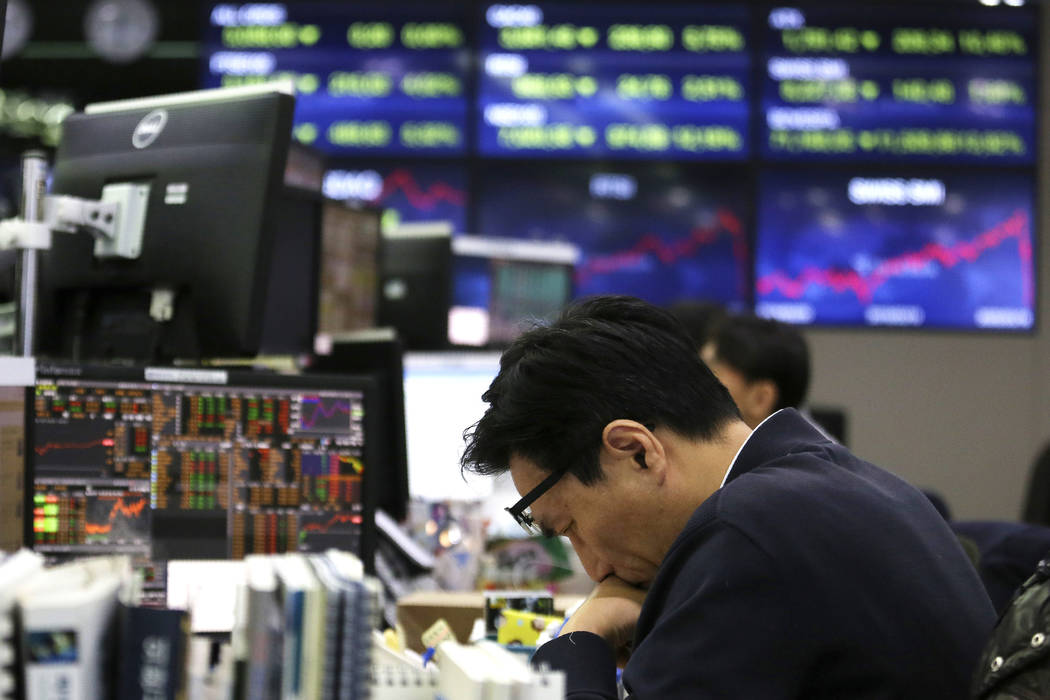 A currency trader drops his head at the foreign exchange dealing room of the KEB Hana Bank head ...
