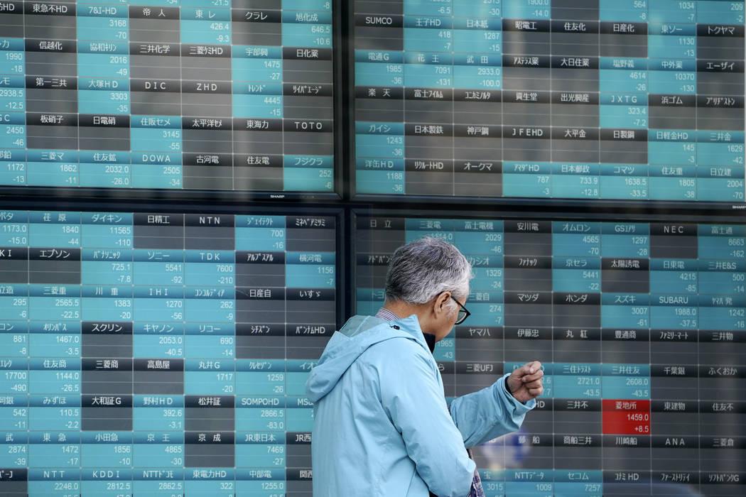 A man walks past an electronic stock board showing Japan's Nikkei 225 index at a securities fir ...