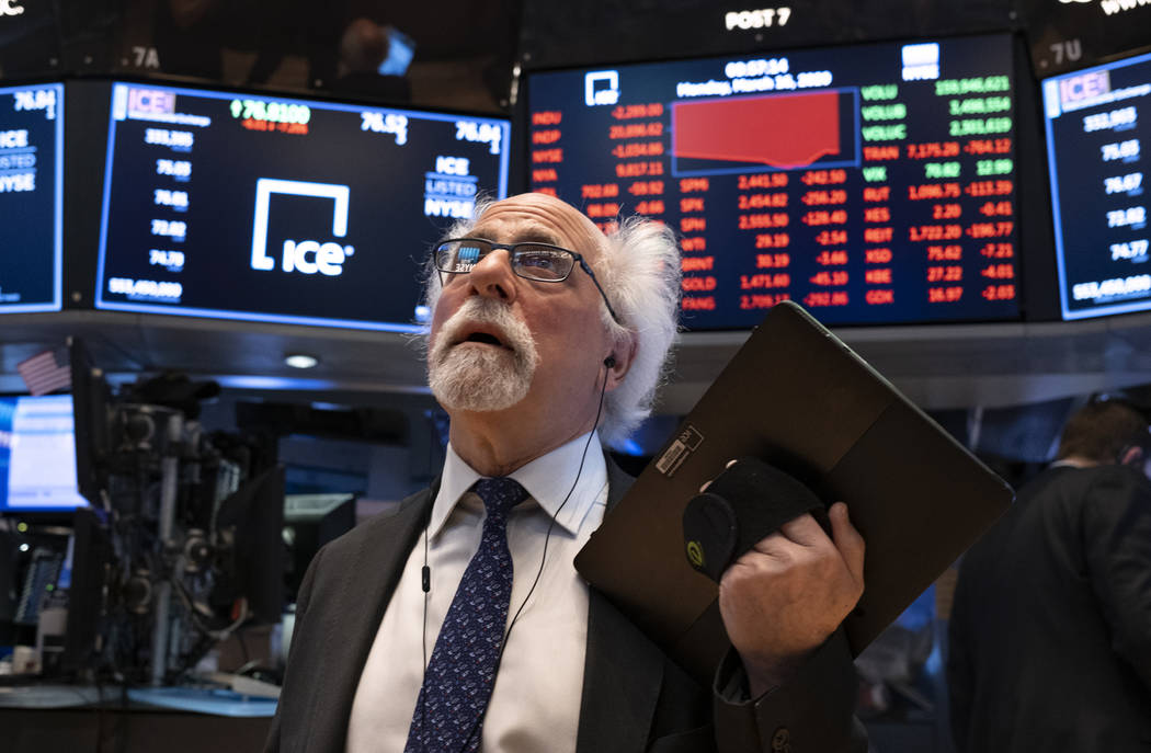 Trader Peter Tuchman works on the floor of the New York Stock Exchange Monday, March 16, 2020. ...