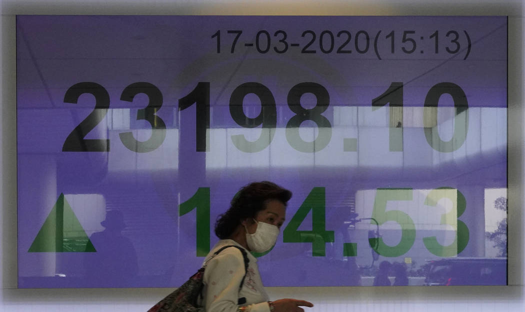 A woman wearing face mask walks past a bank electronic board showing the Hong Kong share index ...