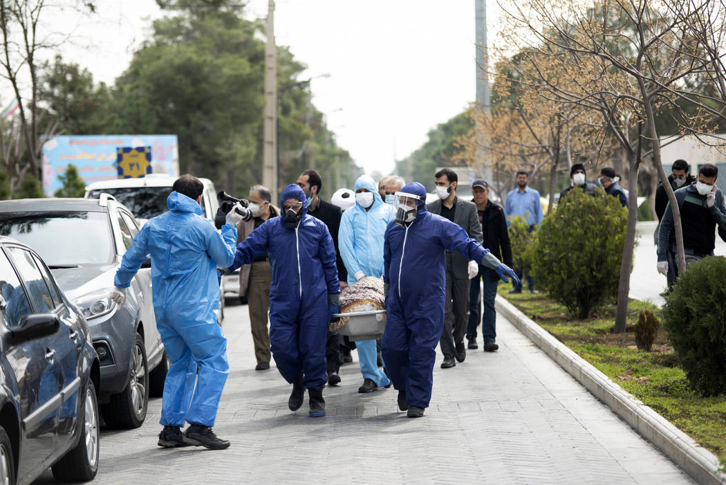 FILE— In this Sunday, March 8, 2020 file photo, men wearing protective gear carry the bo ...