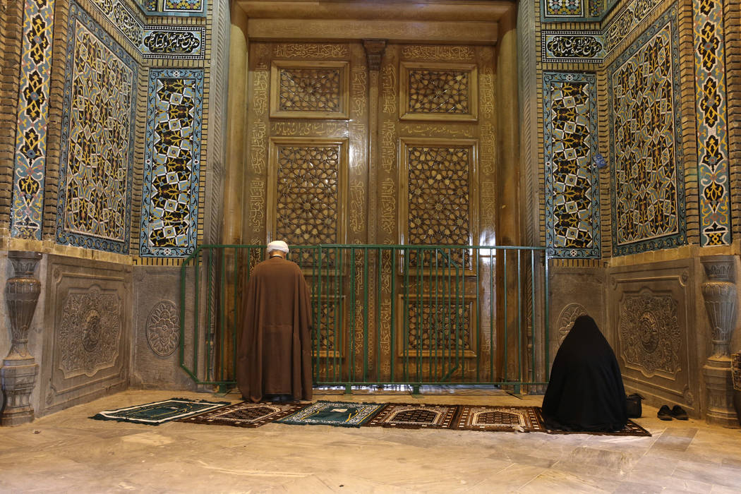 A cleric and a woman pray behind a closed door of Masoume shrine in the city of Qom, some 80 mi ...