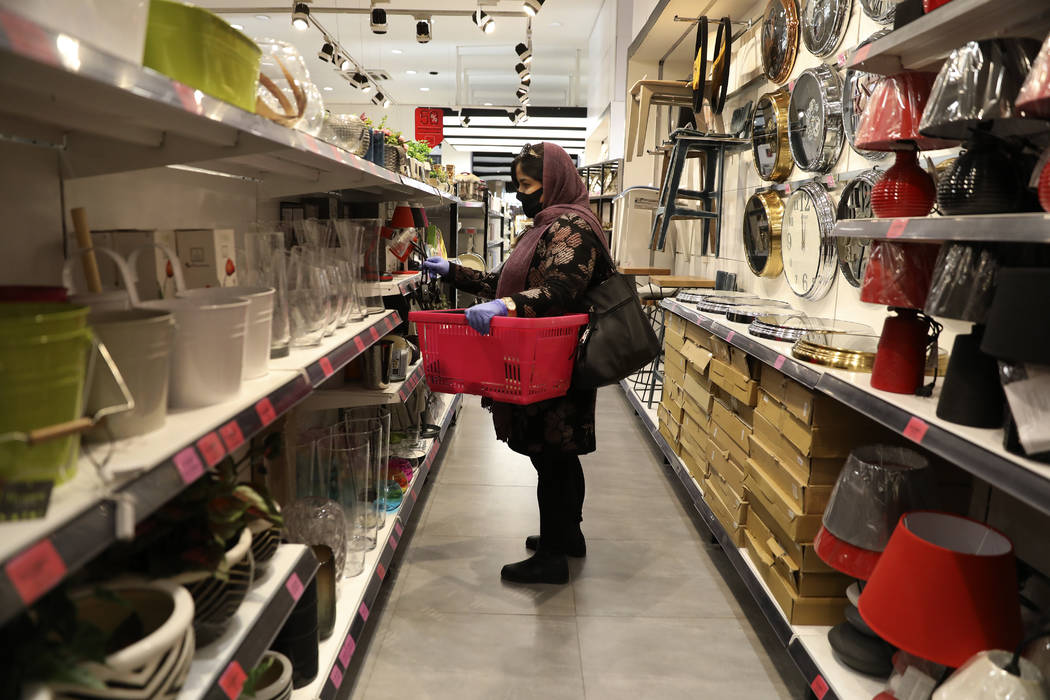 A woman wearing a face mask shops at a store in Bamland shopping mall, in Western Tehran, Iran, ...