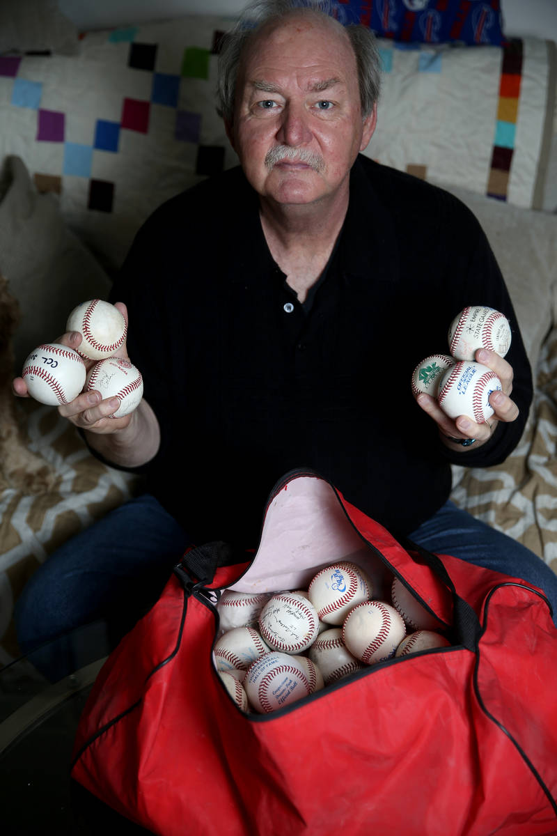 High school umpire Jim Bullock shows collectable baseballs from every league he worked at his L ...