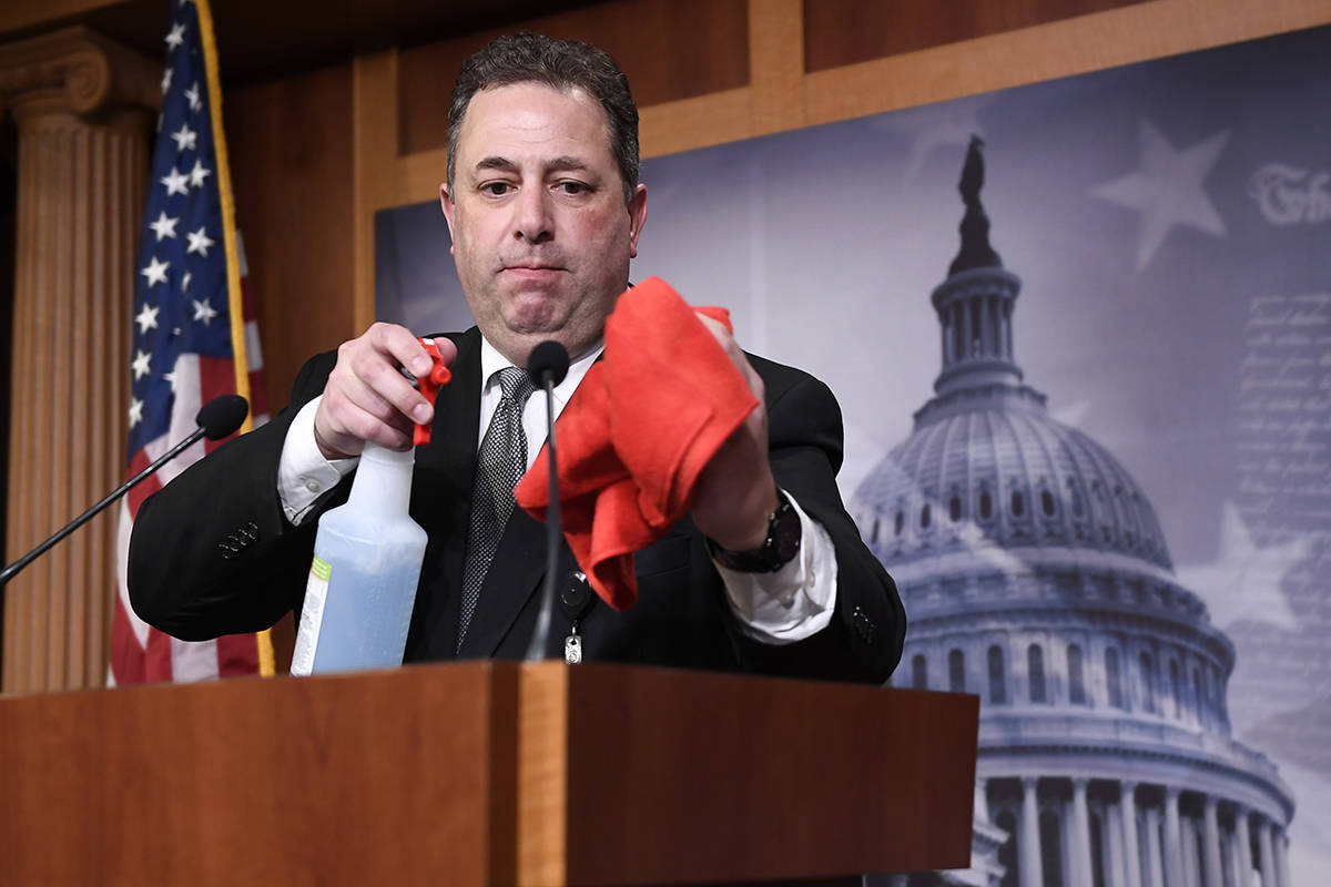 Mike Mastrian, director of the Senate Radio and Television Gallery, cleans down the podium befo ...
