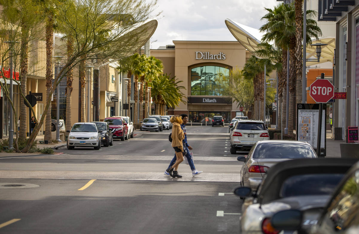 A few shoppers cross the street at Downtown Summerlin which has modified hours and some busines ...