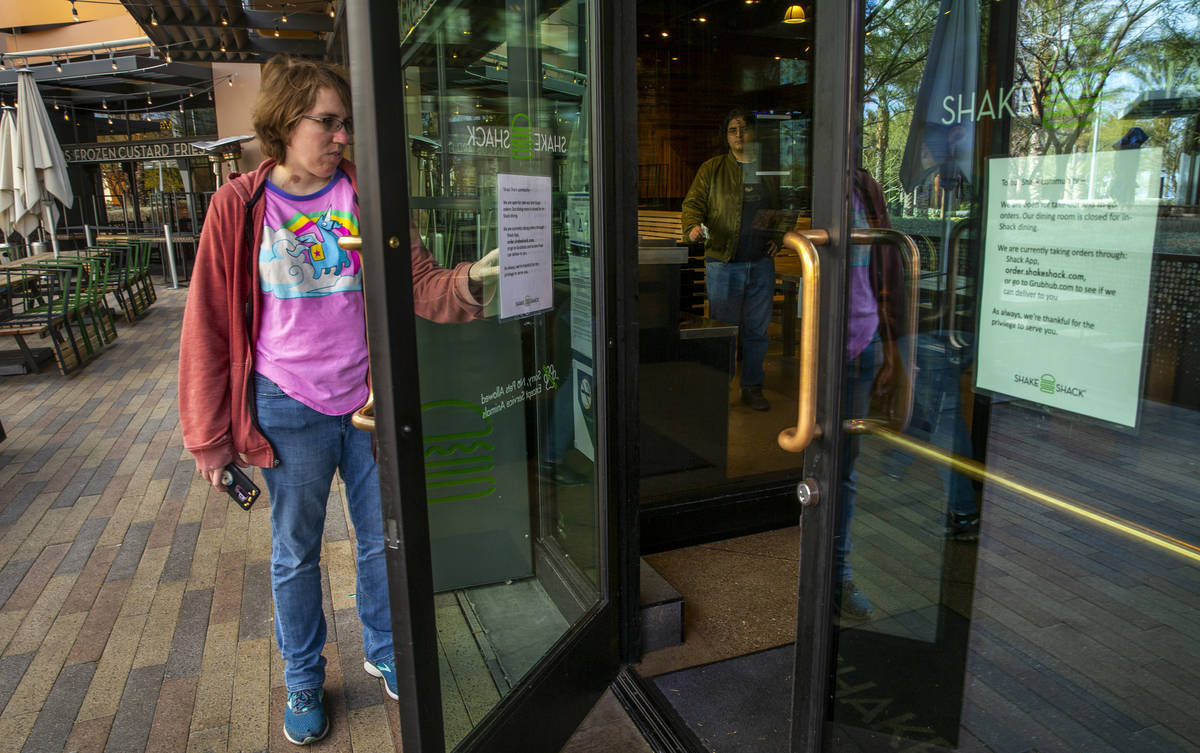 A Shake Shack customer reads the sign outside stating just carryout for the time being at Downt ...