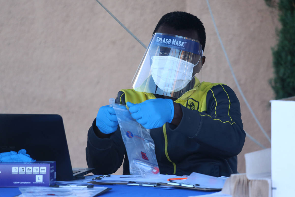 A lab technician processes a collected swab sample at the Sahara Urgent Care & Wellness center ...