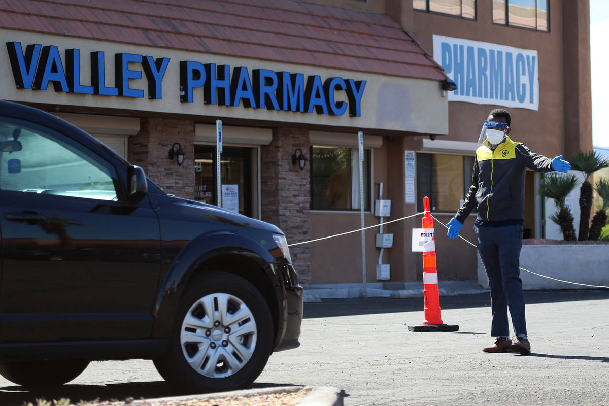 A lab technician directs people at the Sahara Urgent Care & Wellness center in Las Vegas, Tuesd ...