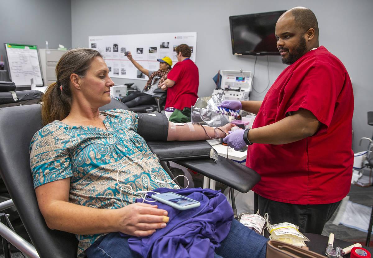 Blood donor Jennaya Fernane, left, has her blood taken by Red Cross team leader Darryl Thompson ...