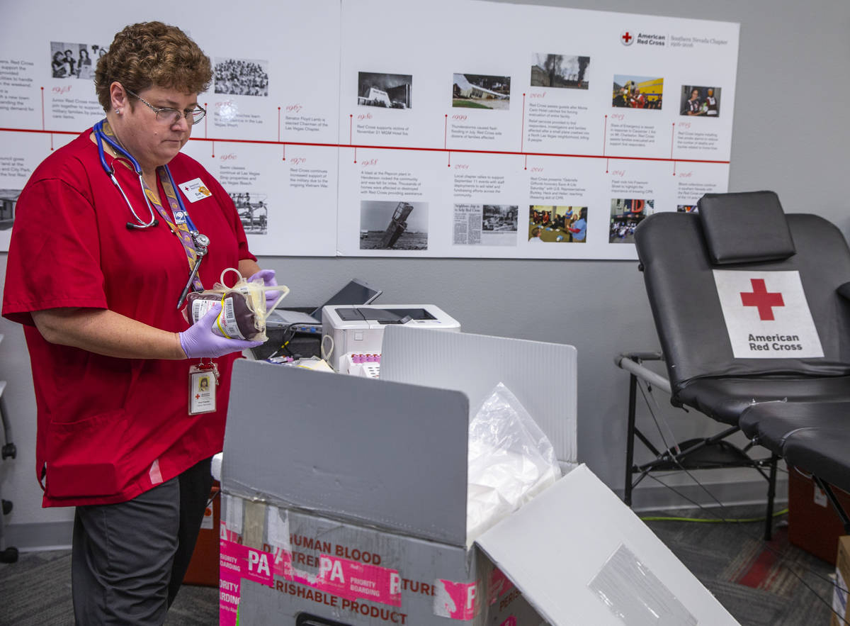 Red Cross team leader Eva Klappa packs new blood donations into a box with ice at the American ...