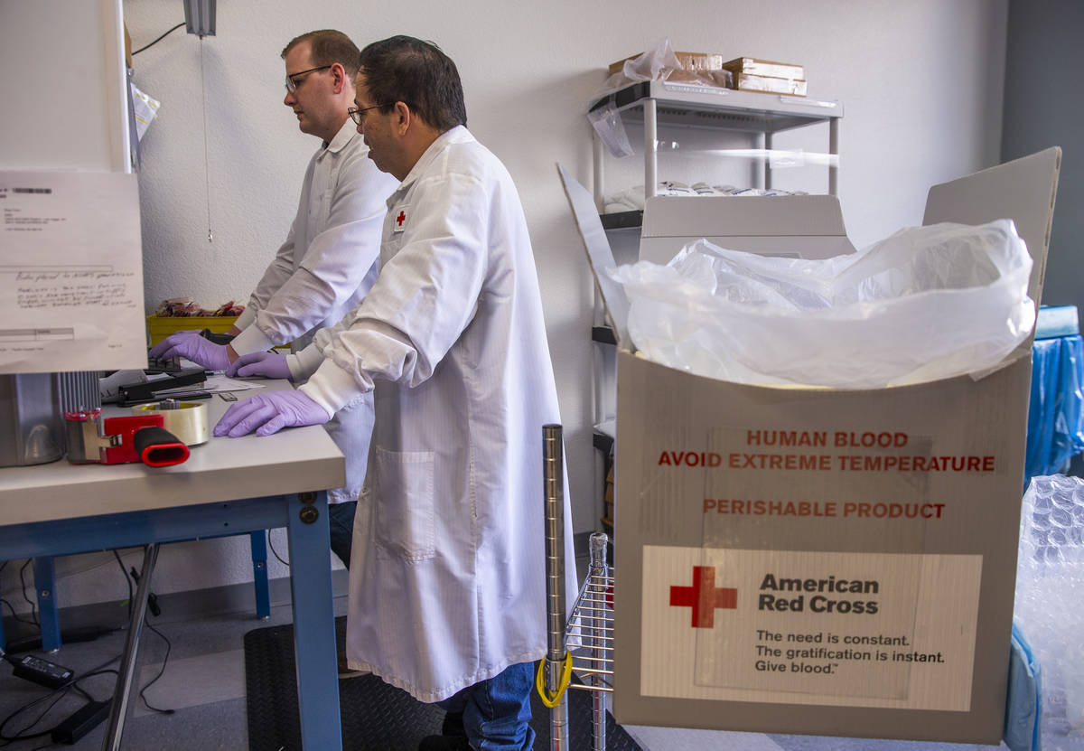 Red Cross team members Rudy Delos-Santos, left, and Kyle Best log in new blood donations and pr ...