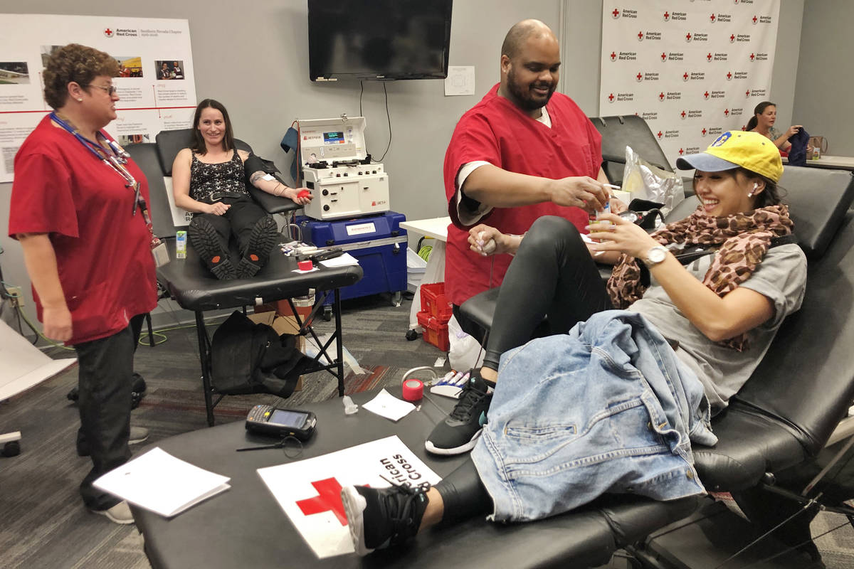 American Red Cross team leader Darryl Thompson Jr., center, draws blood from donor Christy-Anne ...