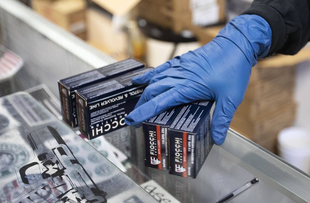 An employee at 2nd Amendment Gun Shop uses gloves while bagging ammunition for a customer on Tu ...