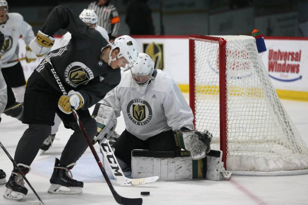 Vegas Golden Knights' Pavel Dorofeyev, left, looks for an open shot against goaltender Jordan K ...