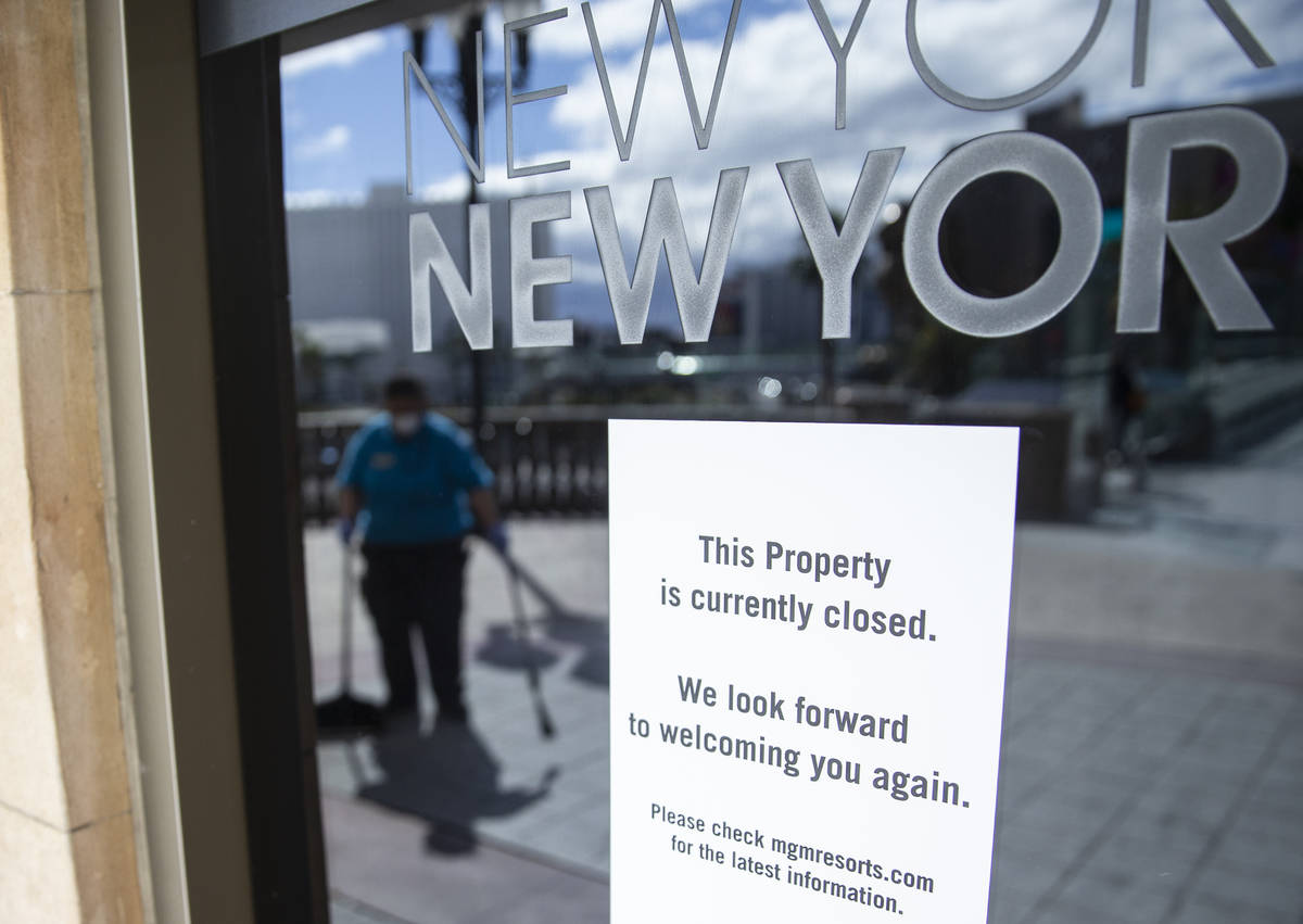 Cleaning staff work outside the doors to New York-New-York where closed signs are posted due to ...