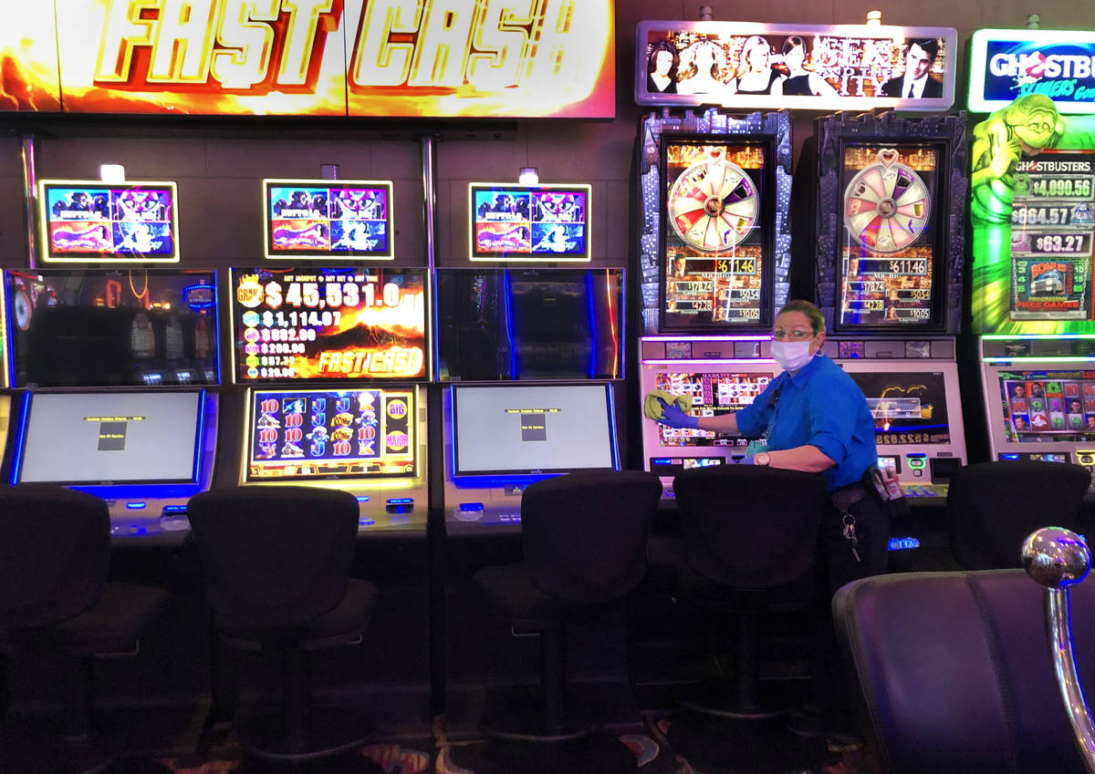 An employee at the Four Queens sanitizes the slots machines on Tuesday, March 17, 2020 in Las V ...