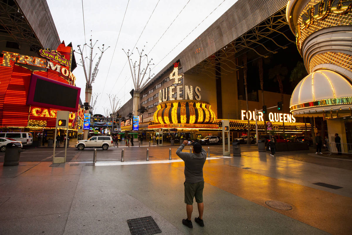 A man takes a photo of the Fremont Street Experience following Gov. Steve Sisolak's statewide o ...