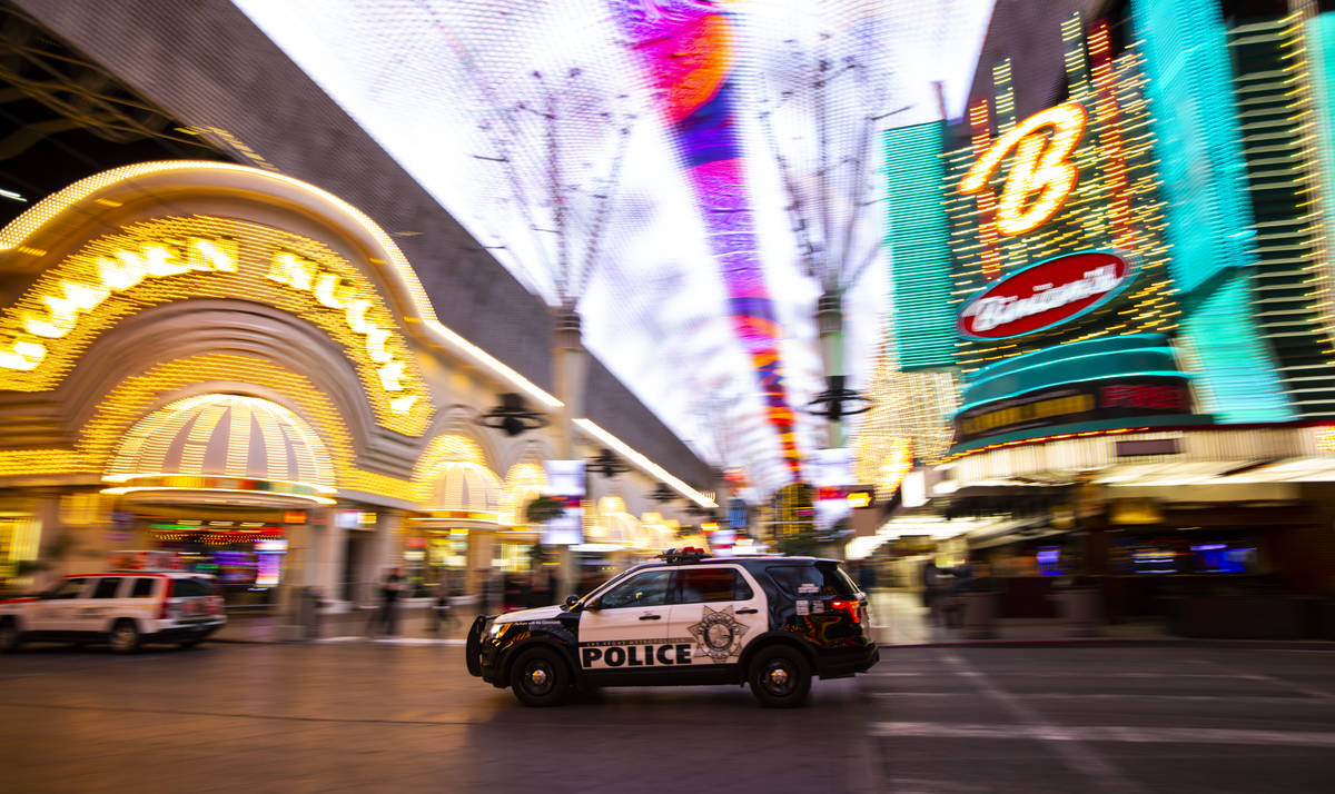 A Las Vegas police vehicle passes the Fremont Street Experience following Gov. Steve Sisolak's ...